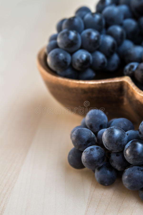 Grapes in a heart shape wooden plate royalty free stock photography