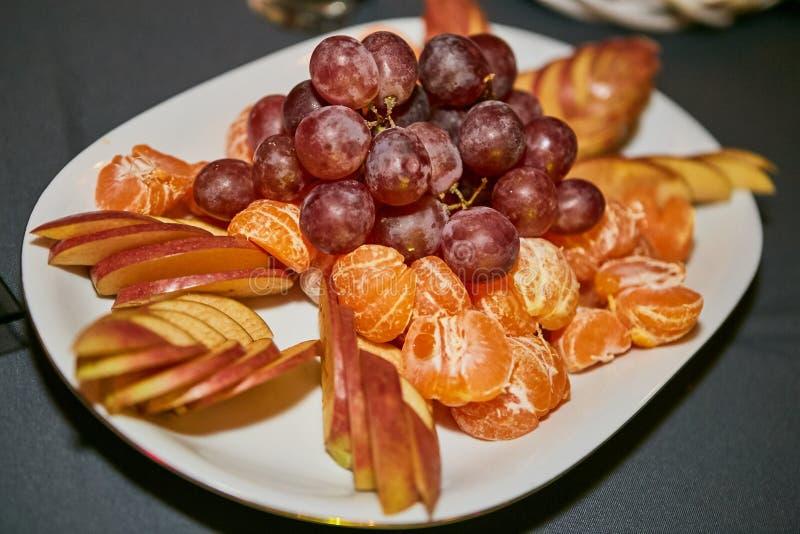 Grapes mandarins apples on plate stock image