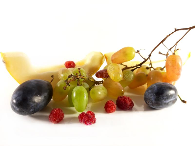 Grapes, plum, raspberries and melon. Fruit and berry on white background. Diet vegetarian food, photo stock photos