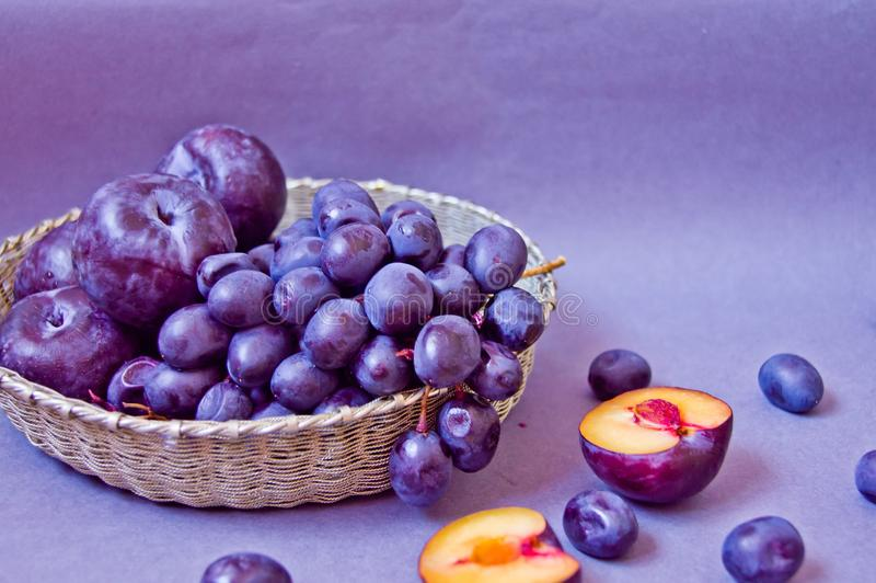 Grapes and plums in a silver basket on a gray background stock image