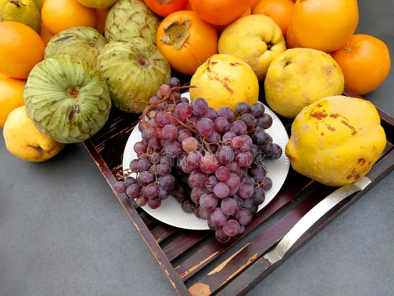 Grapes and autumn fruits in a table. Grapes,quinces and autumn fruits in a table royalty free stock images