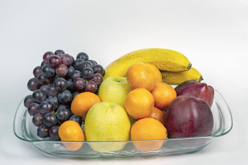 Grapes, red and green apples, tangerines and bananas on a transparent plate. Ripe fruits on a transparent plate stock image