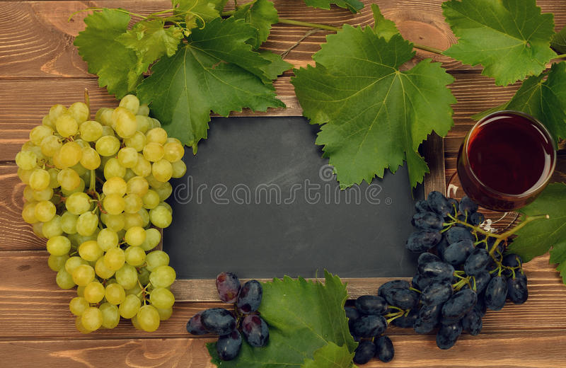 Grapes, wine and writing board. On brown background stock photography