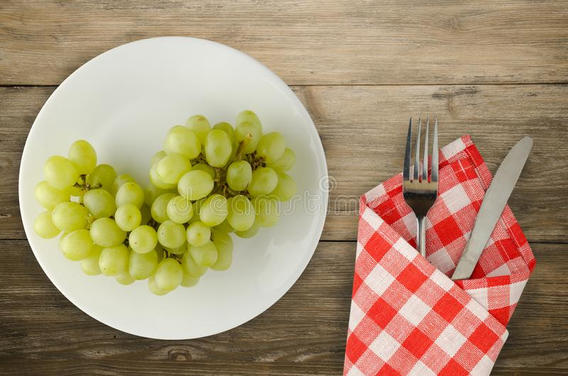 Grapes on a wooden background. grapes on a plate.  royalty free stock photos