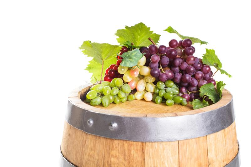 Grapes on wooden barrel. With wine on a white stock photo