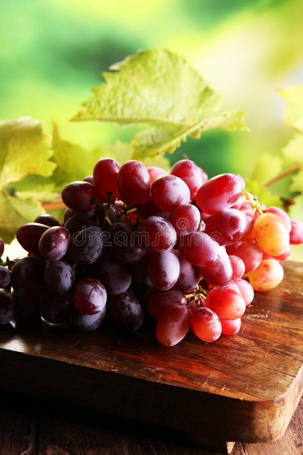 Grapes on wooden table and grape leaves . Healthy fresh fruit wine grapes.  stock photos