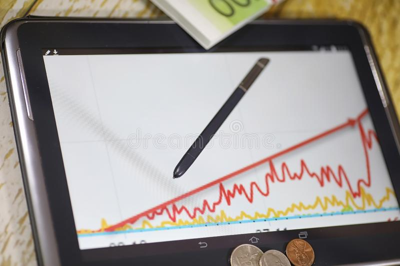 The graph of income growth. Electronic tablet with a graph of gr. Owth rates of profit. The currency on the chart on the smartphone.r stock images