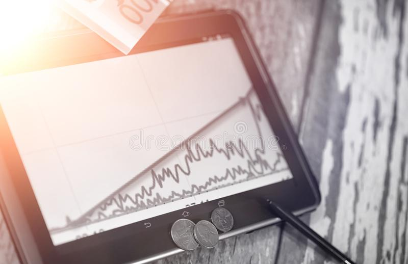 The graph of income growth. Electronic tablet with a graph of gr. Owth rates of profit. The currency on the chart on the smartphone.r stock photos