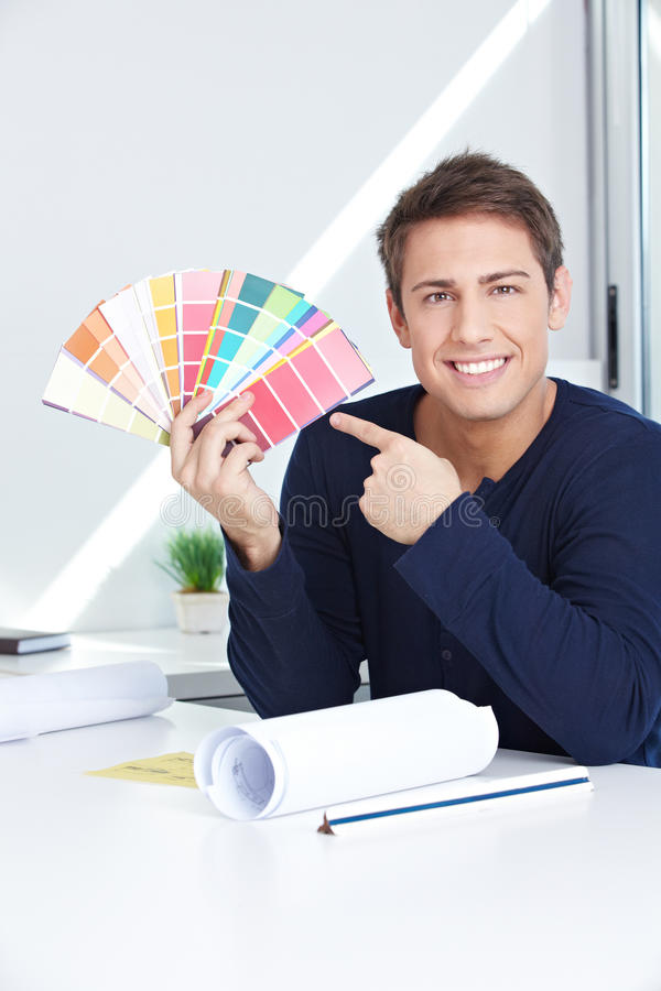 Graphic artist showing color fan. Happy graphic artist in his office showing color fan royalty free stock photo