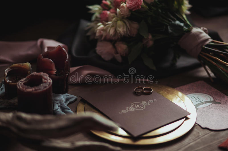 Graphic arts of beautiful wedding pink and brown cards, golden plate with two rings, candles smoke, fabric, bouquet royalty free stock images