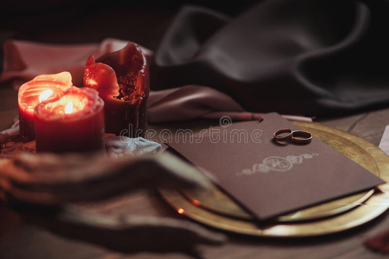 Graphic arts of beautiful wedding pink and brown cards, golden plate with two rings, candles smoke, fabric, snag on wood stock photos