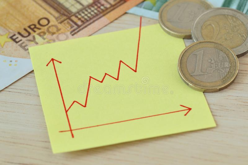 Graphic with ascending line on paper note, euro coins and banknotes - Concept of increasing money value stock photography