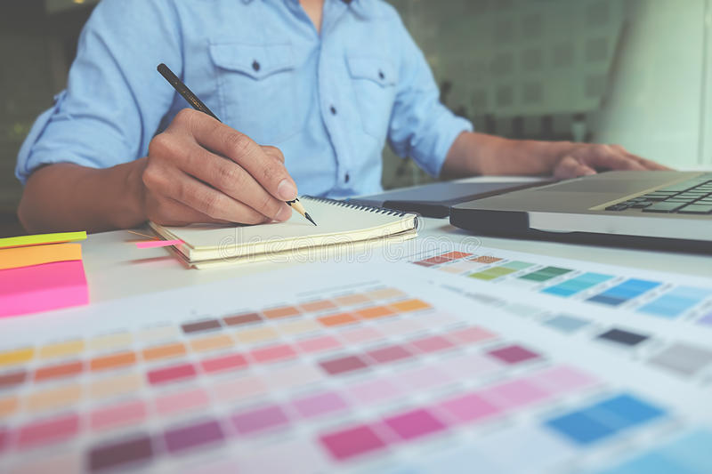 Graphic design and coloured swatches. And pens on a desk royalty free stock images