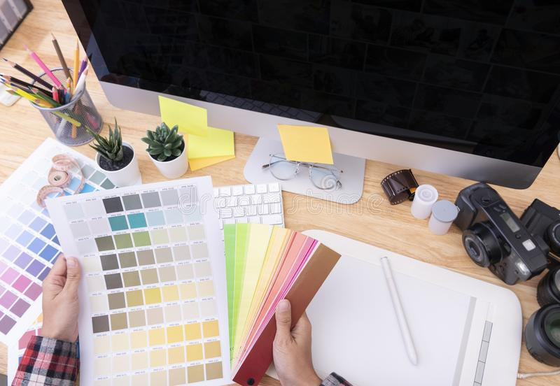 Graphic designer artist creative looking at colour chart at desk in office royalty free stock images