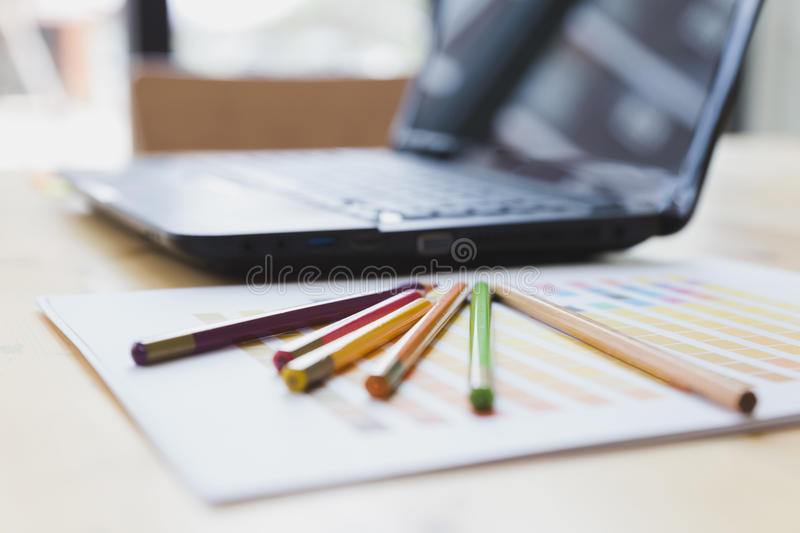 Graphic designer desk table with computer, crayon and color guide palette swatches. Working desk with crayon, color guide palette swatches and laptop computer at royalty free stock photography