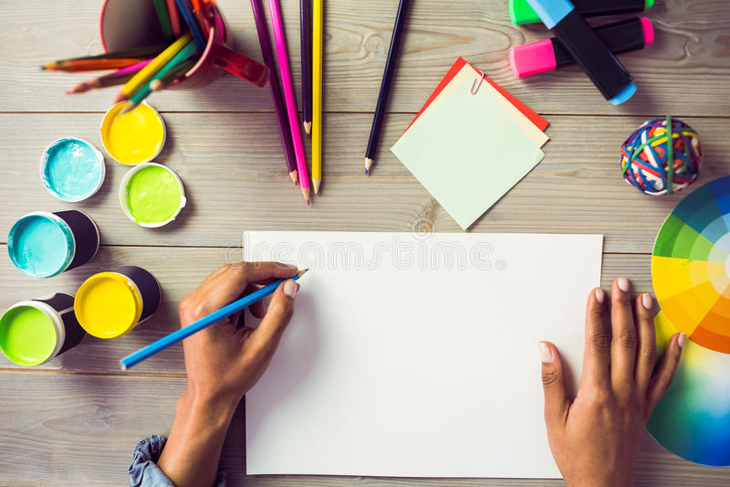 Graphic designer drawing on sheet of paper. At workplace stock image