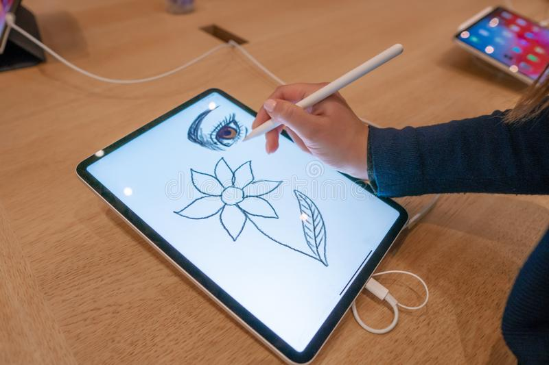 Graphic designer girl drawing sketch on digital tablet screen with stylus pencil royalty free stock image