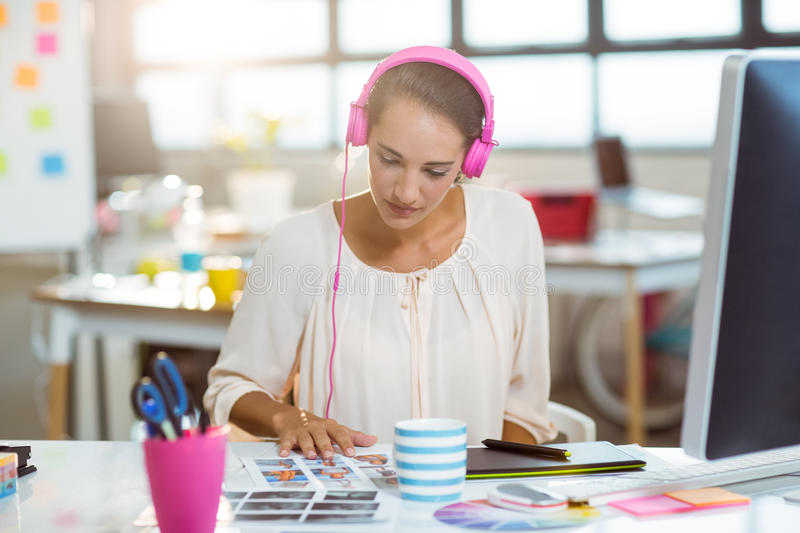 Graphic designer listening to music and looking at color swatch royalty free stock photography
