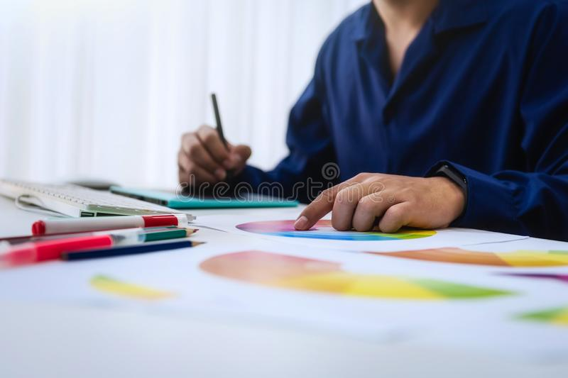 Graphic designer man creative using Color swatch samples for website layout and application for mobile phone in workplace stock images
