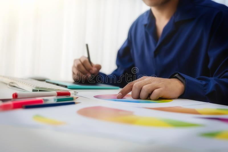 Graphic designer man creative using Color swatch samples for website layout and application for mobile phone in workplace stock photos