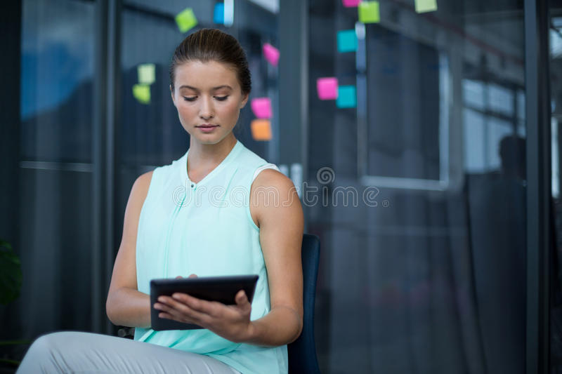 Graphic designer sitting on chair and using digital tablet royalty free stock photo