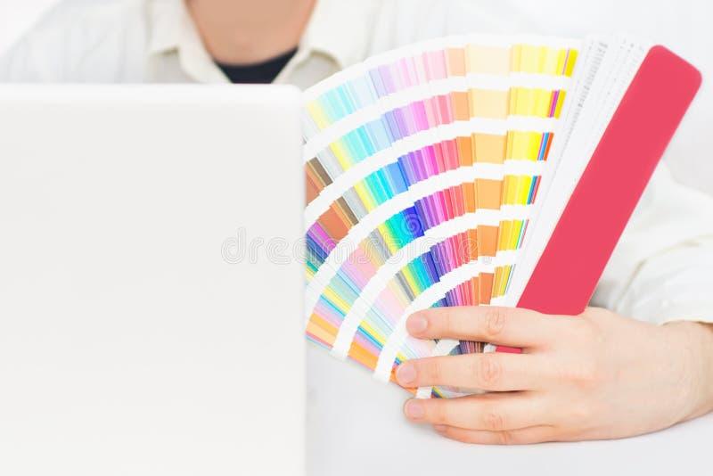 Graphic designer at work. Close up of designer holding pantone palette stock image
