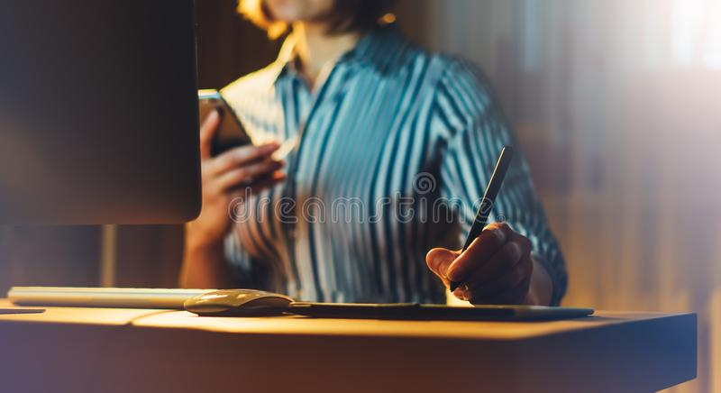 Graphic designer working at office with digital stylus on background monitor computer at night, hipster manager using device pen a stock image