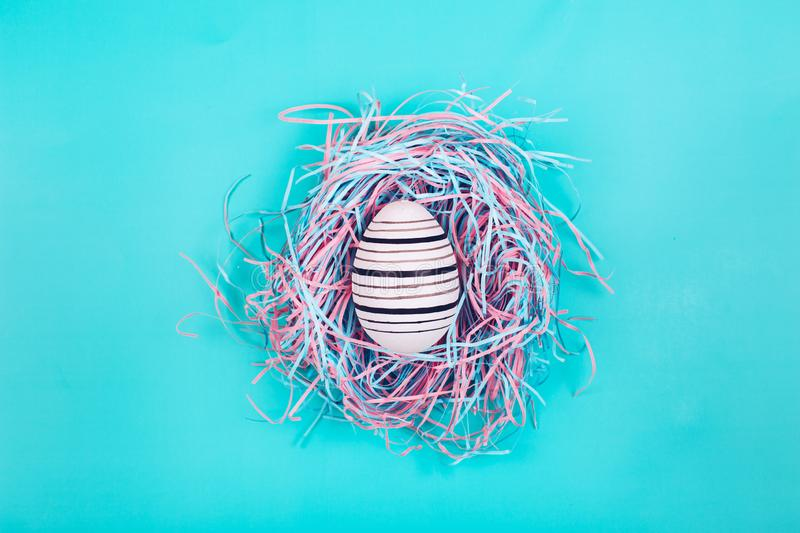 Graphic hand-painted in line egg in decorative nest on blue pastel background. stock photography