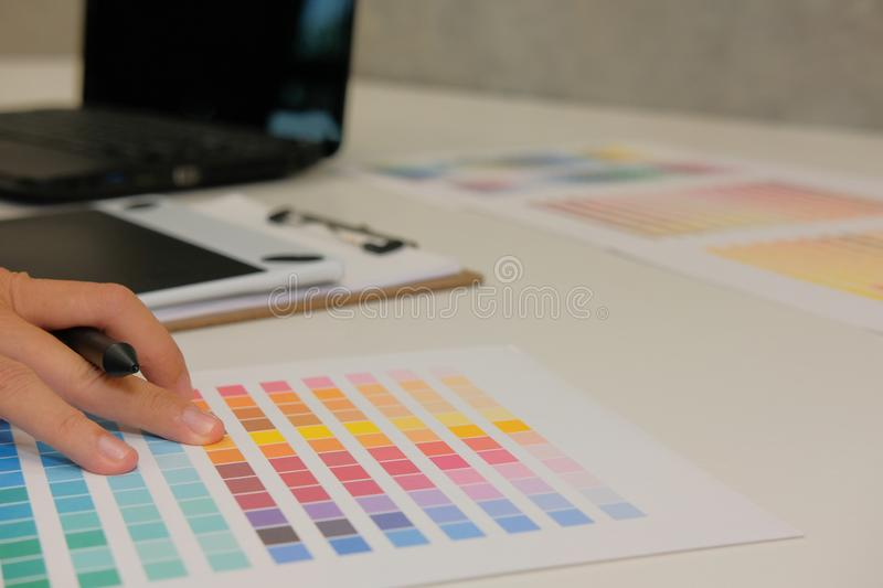 Graphic interior designer choosing color from swatch sample catalogue palette guide. artist design & idea for creativity project. Graphic interior designer royalty free stock photography