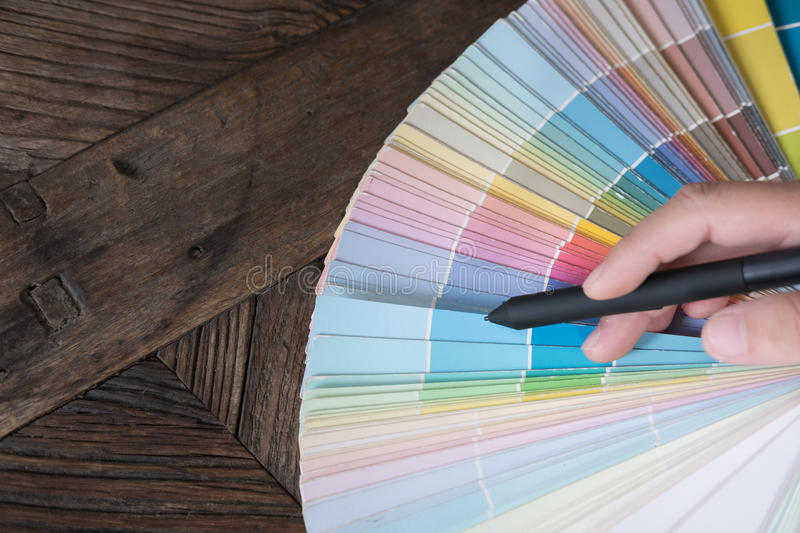 Graphic or interior designer choosing a colour from color swatch royalty free stock photography