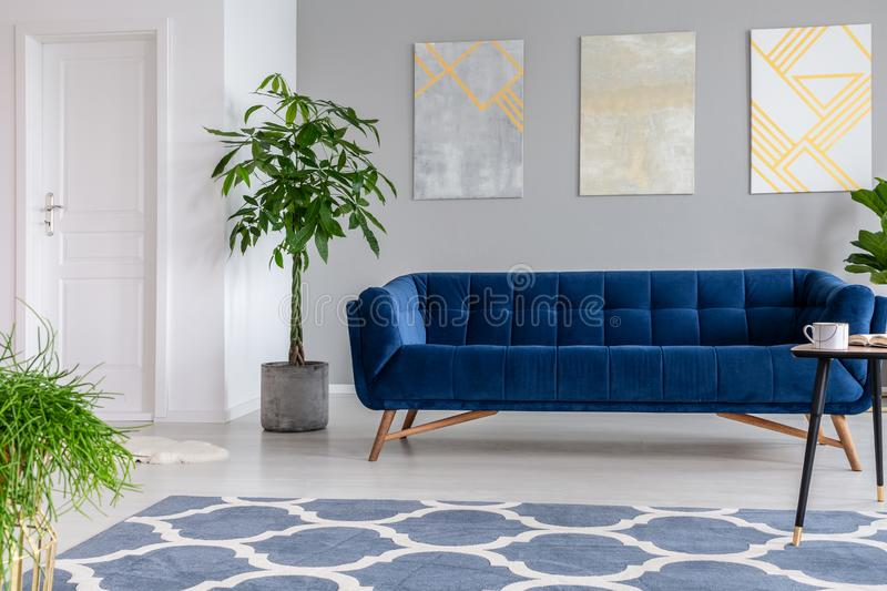 Graphic paintings on a gray wall behind a luxuries velvet dark blue couch in an elegant living room interior with gold accents. Re. Al photo. concept royalty free stock photography