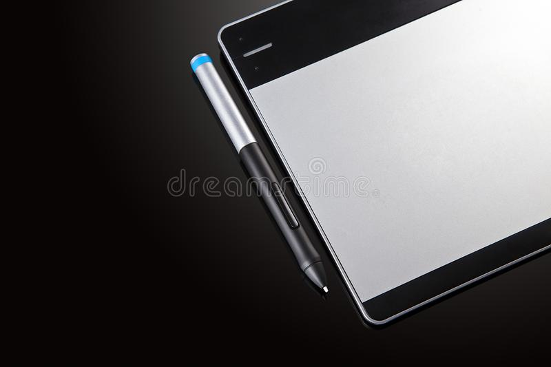 Graphic tablet with pen on black background royalty free stock photos