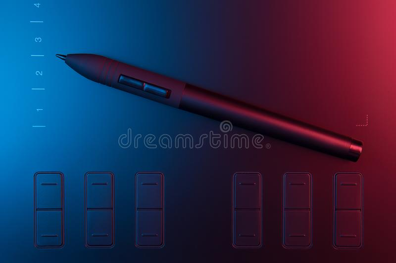 Graphic tablet with pen for illustrators and designers on black wooden background. stock photos