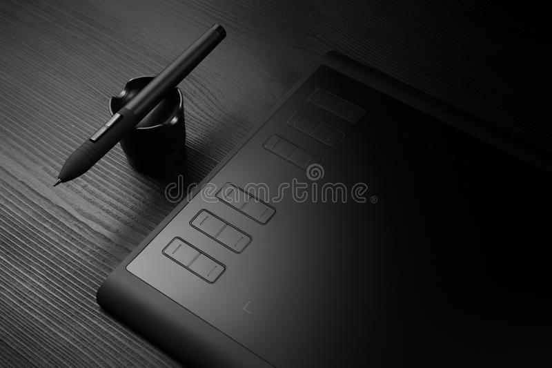 Graphic tablet with pen for illustrators and designers on black wooden background. stock photo