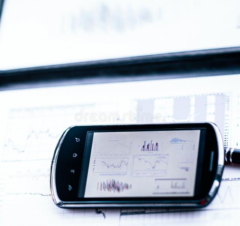 Graphique de gestion avec un téléphone intelligent et un stylo sur un bureau dans  photographie stock libre de droits