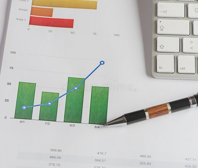 Graphiques couleur sur des finances et des affaires avec un clavier de stylo et d'ordinateur photo libre de droits