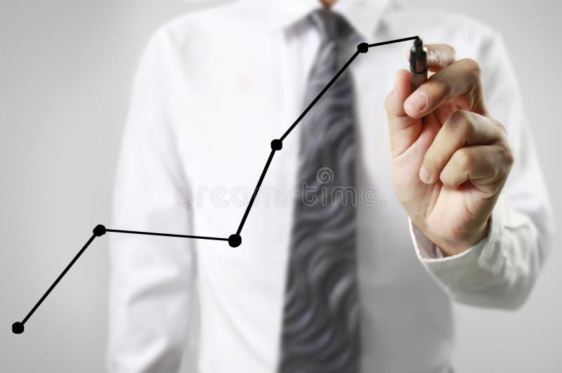 Graphiques de dessin d'homme d'affaires élevant le graphique photo stock