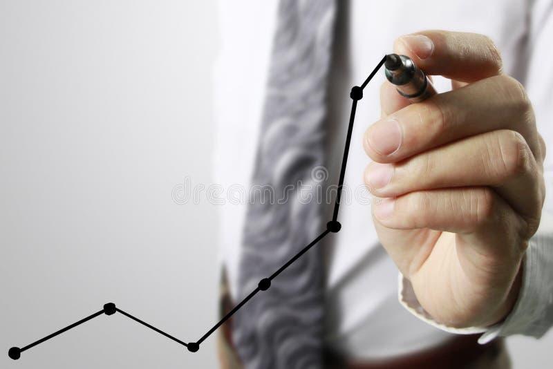 Graphiques de dessin d'homme d'affaires élevant le graphique photographie stock