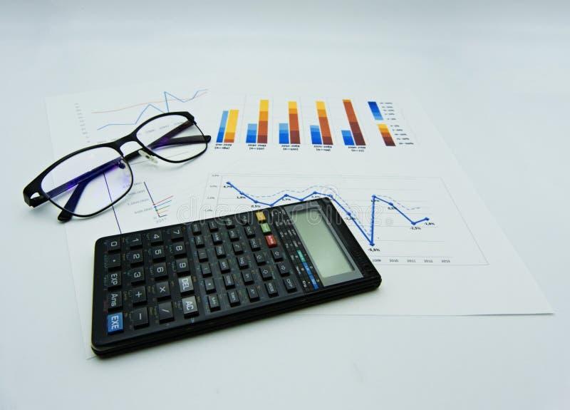 Graphiques de données et diagrammes, verres et calculatrice, fond blanc images libres de droits