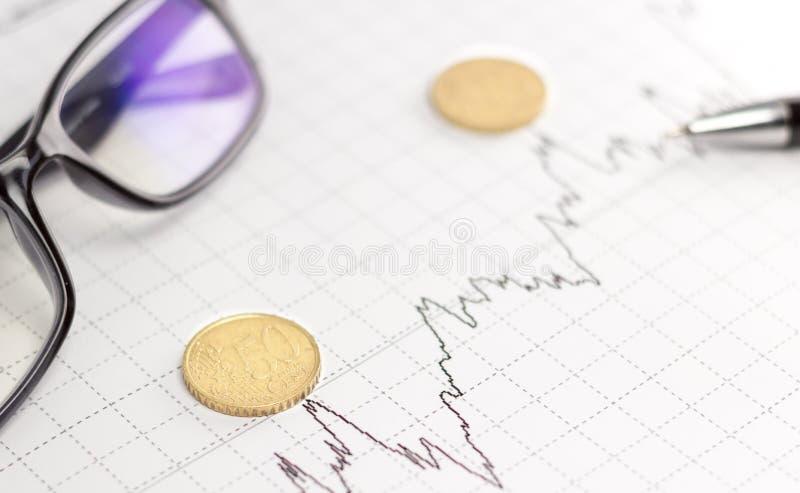 Graphiques, verres, calculatrice et pièces de monnaie sur le bureau photographie stock