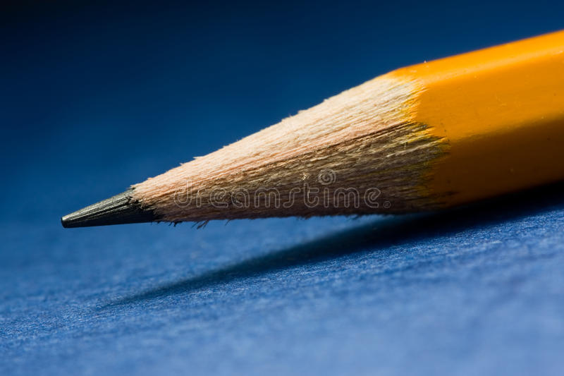 Graphite pencil on blue background. Macro of sharpened lead pencil stock photography