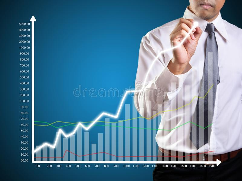 Graphs. Business man hand drawing a graph, shares, market, leadership, , forecasting, copy, white, achievement, sketching, future, consultant, blank, whiteboard royalty free stock image