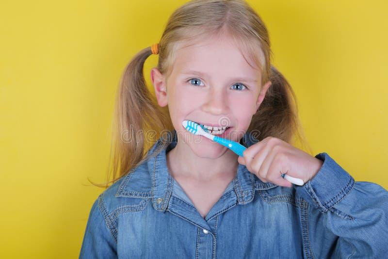 Grappig blond meisje die haar tanden op gele achtergrond borstelen Kindgezondheidszorg, mondeling hygiëneconcept royalty-vrije stock foto's
