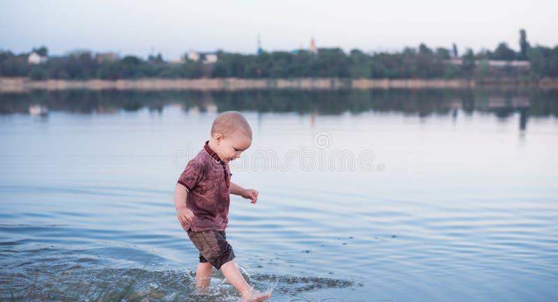 Grappig blonde weinig jongen die in een mooie rivier op de lentedag bespatten stock foto's