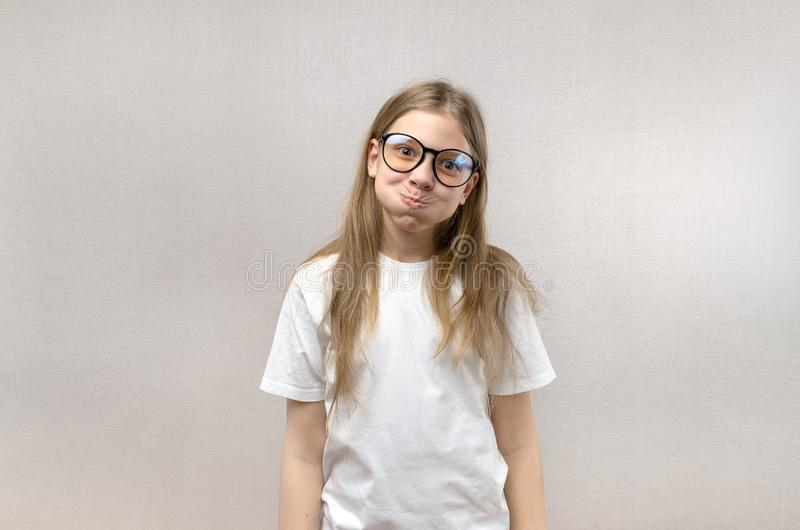 Grappig blondemeisje in glazen die haar gezicht kronkelen, nabootsend, hebbend pret Close-up stock fotografie