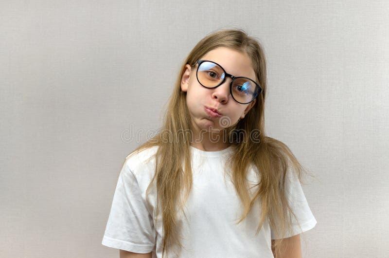 Grappig blondemeisje in glazen die haar gezicht kronkelen, nabootsend, hebbend pret Close-up royalty-vrije stock afbeeldingen