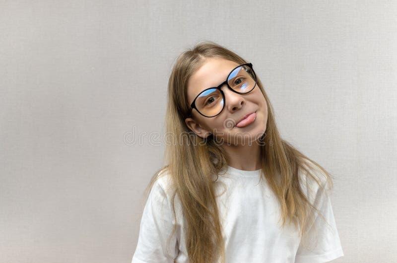 Grappig blondemeisje in glazen die haar gezicht kronkelen, nabootsend, hebbend pret Close-up royalty-vrije stock foto