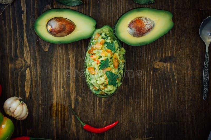 Grappig die voedselgezicht van avocado en guacamole onderdompeling wordt gemaakt royalty-vrije stock foto