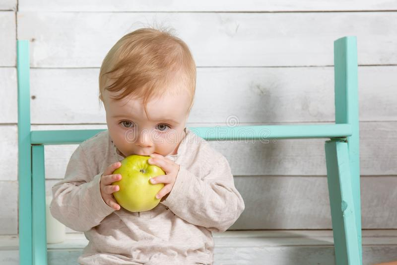 Grappig eet weinig blonde babyjongen grote groene appelzitting op de houten stappen en de houten achtergrond stock afbeeldingen