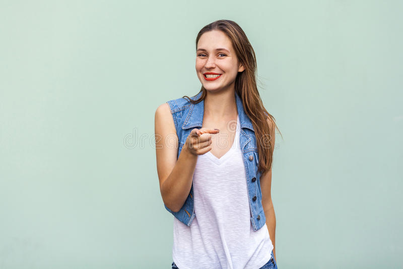 Grappig freckled meisje in toevallige witte t-shirt en jeans jecket, richtend vinger op camera en toothy glimlach royalty-vrije stock afbeelding